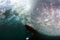 Surfing view from underwater. A view from underwater of a longboarder surfing a wave in hawaii royalty free stock image