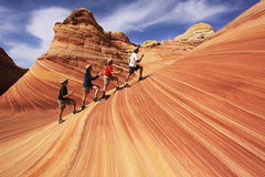 Surfing The Wave. Four hikers having some whimsical fun at The Wave in the Coyote Buttes section of the Paria Canyon-Vermilion Cliffs Wilderness in northern Royalty Free Stock Photo