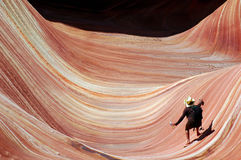 Surfing the wave. Woman in yellow cowboy hat in mock surfing pose on the wave Stock Photos