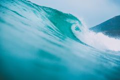 Blue surfing wave breaks in the ocean Stock Images