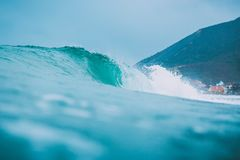 Blue wave in ocean. Surfing swell and cloudy sky Stock Image