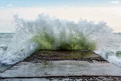 Surfing wave breaks with splashes against spurdike during the storm on Black Sea coast.  royalty free stock image