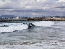 Surfers catching Waves in Costa da Caparica. royalty free stock photography