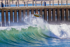 Surfing Wave Rider Air. Surf rider does a air turn above hollow wave at new pier beach Durban Stock Images