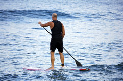 Surfing the Waves. Tom Thayer taking a break and surfing with an oar stock photography