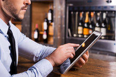 Surfing web in bar. Close-up of man in shirt and tie working on digital tablet while sitting at the bar counter royalty free stock photography