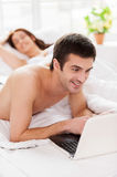 Surfing web in bed. Royalty Free Stock Photography