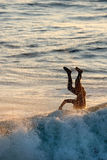 Surfing Wipe-out. A silhouette of a surfer landing head first into the water Stock Image