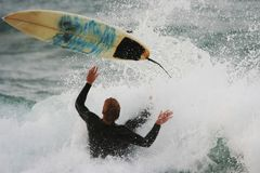 Surfing Wipeout. Young man falling off his surfboard on an ocean wave Royalty Free Stock Photos