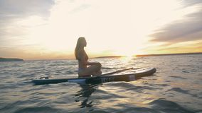 One woman floats on waves, meditating, side view. Surfing woman sits on her board in a pose, resting. Surfing woman sits on her board in a pose, resting stock video