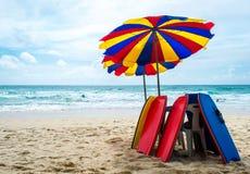 Surfingbräda och paraply på stranden royaltyfri bild