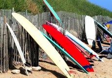 Surfingbrädor som vilar upp på ett staket i dikeslättar Arkivbild