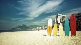 Surfingbrädor som står i ljus sol på Ipanema, sätter på land Arkivfoto