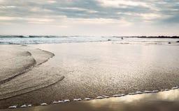 Surfingman tiny figurine on ocean beach at sunrise time Stock Photos