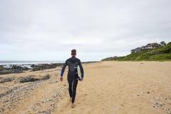 Surfingowiec chodzi wzdłuż plaży z surfboard obrazy royalty free