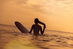 Surfingowiec dziewczyna w oceanie przy zmierzchu czasem Zdjęcia Royalty Free
