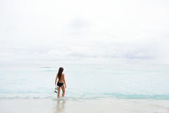 Surfingowiec dziewczyny iść surfować patrzejący ocean plażę Fotografia Royalty Free