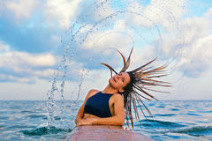 Surfingowiec dziewczyny trzepnięcia długi mokry włosy z pluśnięciami w powietrzu obrazy stock