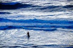 Surfingowiec kroczy w kierunku dużych fala w niespokojnym morzu przy półmrokiem Zdjęcia Royalty Free