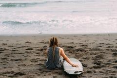 Surfingowiec z dreadlocks z surfingboard blisko oceanu obrazy stock