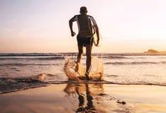 Surfingowiec z surfboard biega wewnątrz ocean fala Obrazy Stock