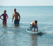 Surfingowowie i ich syn iść surfować w oceanie w słonecznym dniu Zdjęcie Stock