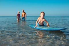 Surfingowowie i ich syn iść surfować w oceanie w słonecznym dniu Zdjęcie Royalty Free