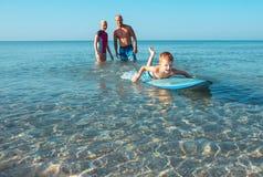 Surfingowowie i ich syn iść surfować w oceanie w słonecznym dniu Obraz Stock