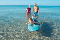 Surfingowowie i ich syn iść surfować w oceanie w słonecznym dniu Zdjęcia Stock
