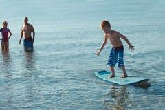Surfingowowie i ich syn iść surfować w oceanie w słonecznym dniu Zdjęcia Royalty Free