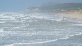 Surfingowowie i kitesurfers przy plażą zbiory