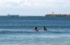 Surfingowowie i naczynie przeciw Błękitnemu Chmurnemu niebu Zdjęcia Royalty Free