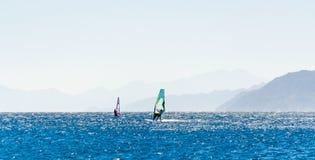 Surfingowowie jadą w Czerwonym morzu w Egipt przeciw tłu skalisty wybrzeże fotografia stock