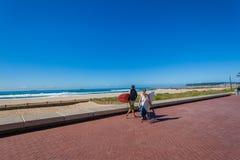 Surfingowowie Męski Żeński Chodzący Beachs Machają morze Obrazy Stock
