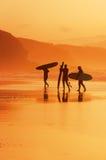 Surfingowowie na brzeg przy zmierzchem Zdjęcie Royalty Free