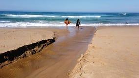 Surfingowowie niesie surfboards na ocean spokojny plaży, Australia