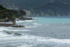 Surfingowowie w szorstkim morzu przy Ventigmiglia w północnym Włochy Obrazy Royalty Free