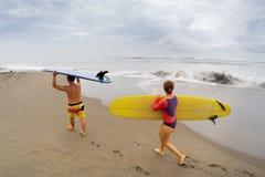 Surfingowowie z deską Obrazy Royalty Free