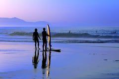 Surfingowowie z zmierzchu odbiciem na surfboard Obraz Stock