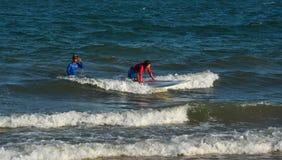Surfista allegro del principiante della giovane donna fotografia stock
