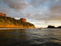 Surfista a bordo que espera um passeio no oceano fora da costa montanhosa da rocha de Magnific, Nicarágua na frente de duas casas Fotografia de Stock