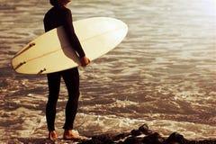 Surfista che entra nell'oceano all'alba Fotografia Stock