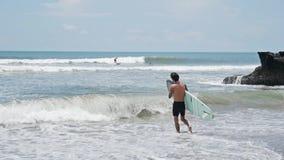 Surfista che entra in rallentatore dell'oceano stock footage