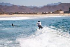 Surfista che guida un'onda con la spiaggia nei precedenti immagine stock