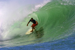Surfista Clyde Lani che pratica il surfing un'onda della tubazione immagine stock libera da diritti