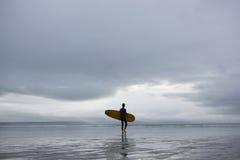 Surfista com prancha que anda para o mar na praia Imagens de Stock