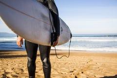Surfista con il suo bordo sulla spiaggia immagini stock libere da diritti
