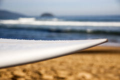 Surfista con il suo bordo sulla spiaggia immagine stock