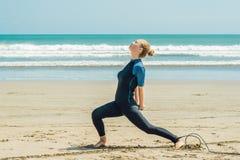 Surfista da jovem mulher que aquece-se na praia antes de surfar fotos de stock