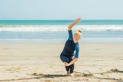 Surfista da jovem mulher que aquece-se na praia antes de surfar imagem de stock